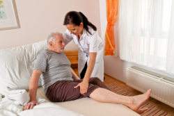 caregiver helping an elderly man getting up from bed