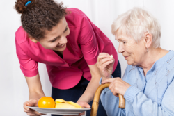 caregiver serving food to and elderly woman