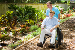 elderly man in wheelchair with his caregiver